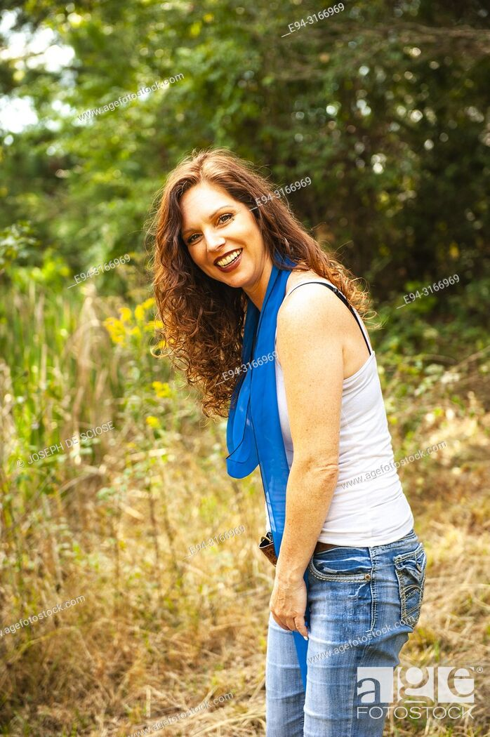 Stock Photo: A pretty 39 year old redheaded woman on a country road, smiling at the camera .