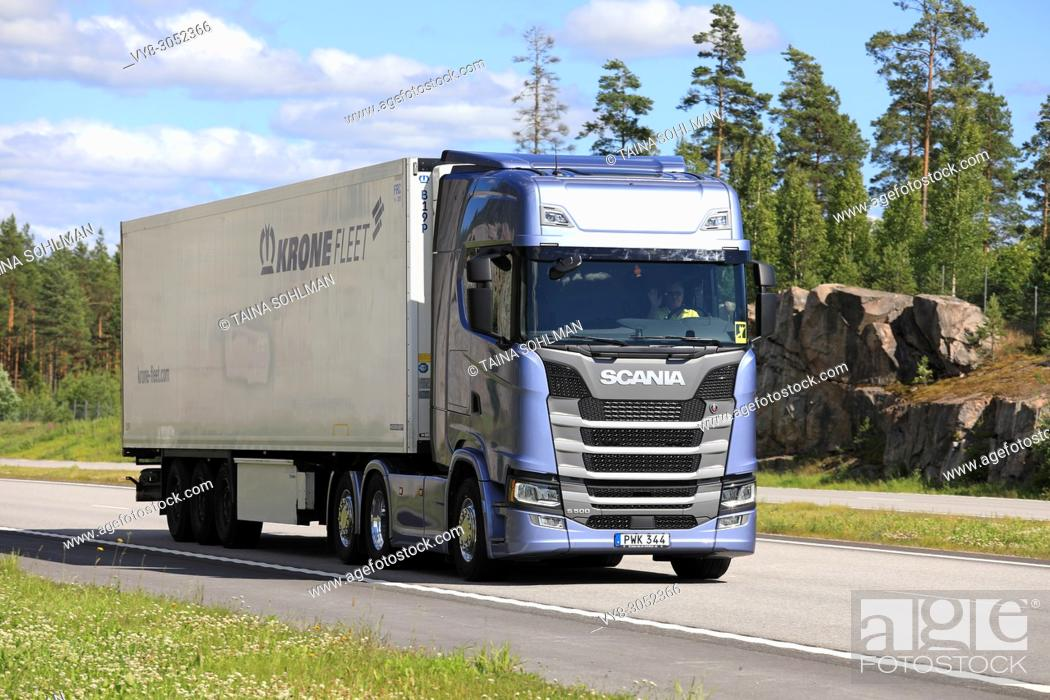 Stock Photo: Ice blue Next Generation Scania S500 semi trailer delivers load along E18 motorway in South of Finland on a beautiful day of summer.