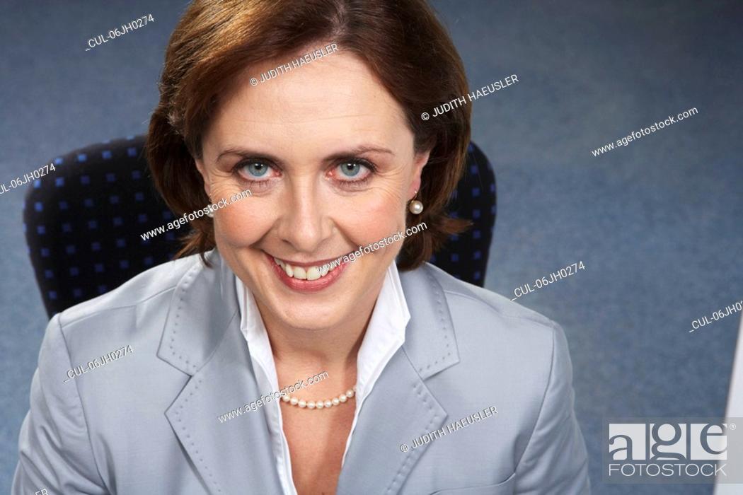Stock Photo: Portrait of mature businesswoman, smiling.
