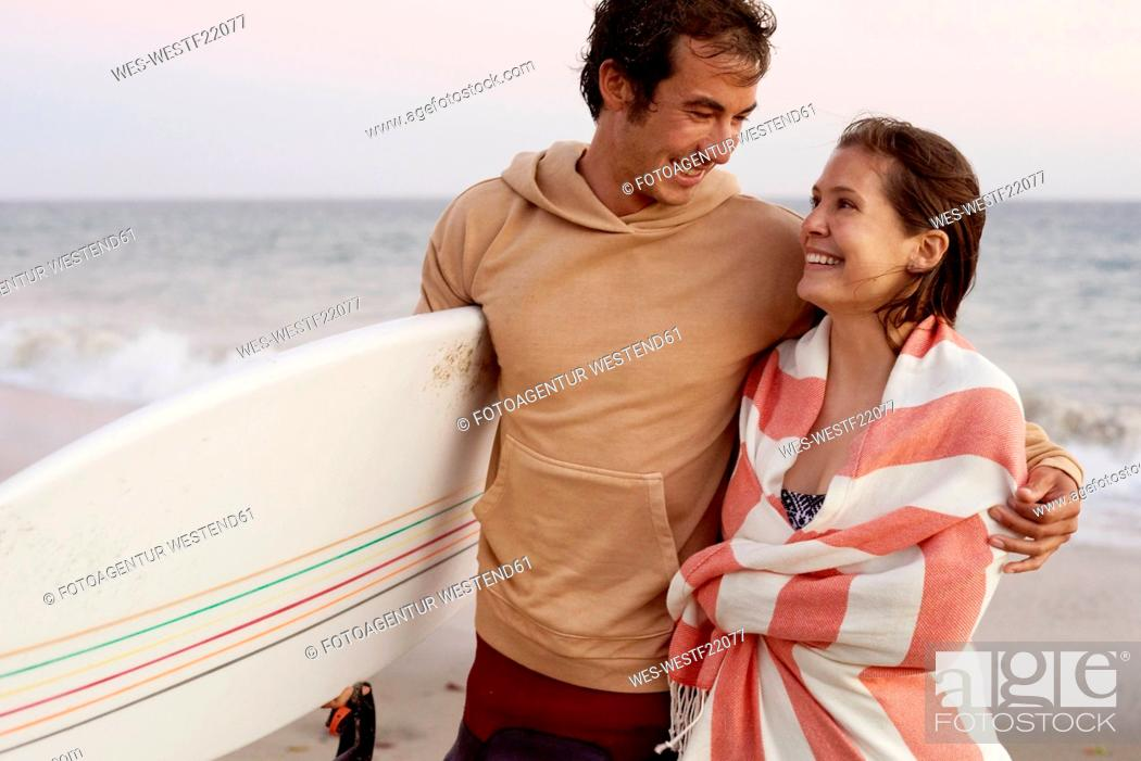 Stock Photo: Smiling young couple on the beach carrying surfboard.