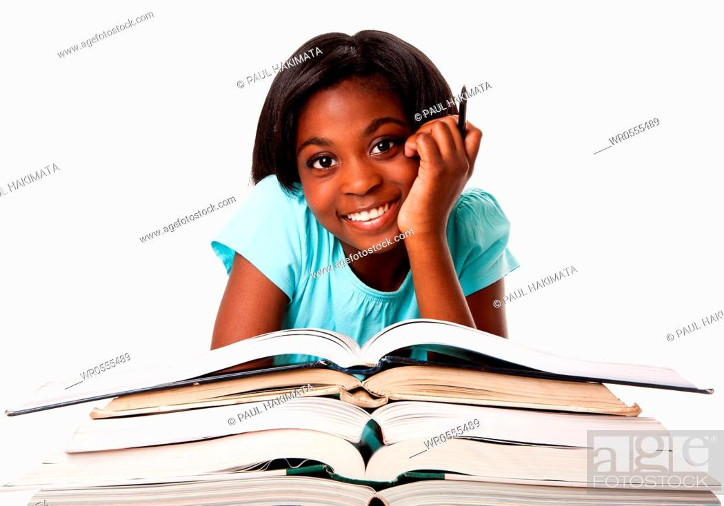 Imagen: Beautiful happy smiling student with pen and a pile of open books doing homework, isolated.