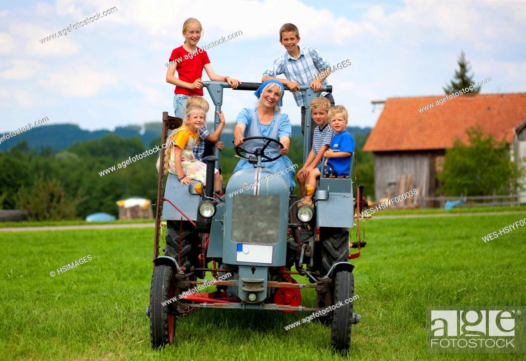 Stock Photo: Germany, Bavaria, Woman with group of children sitting on old tractor in front of farmhouse.