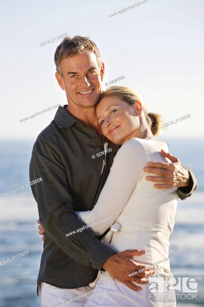 Stock Photo: Mature couple embracing on beach, smiling, portrait.
