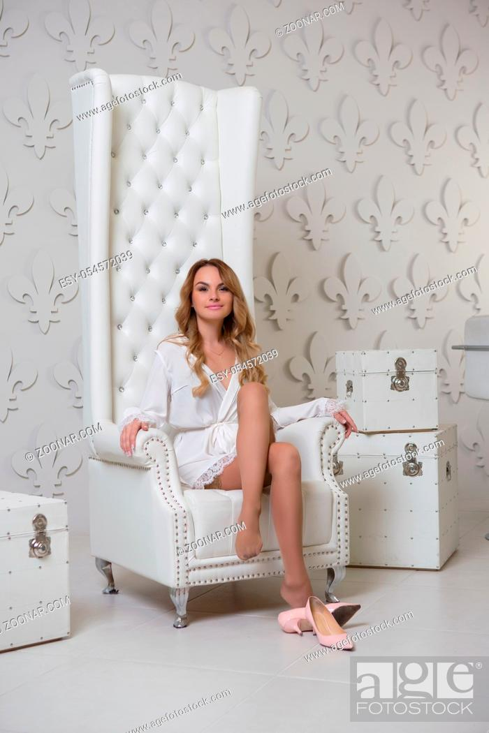 Stock Photo: Sexy lady posing in studio sitting in a chair and wearing a white bathrobe.