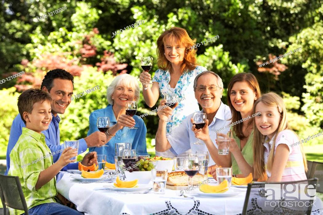 Stock Photo: Family sitting at table for lunch in back yard portrait.