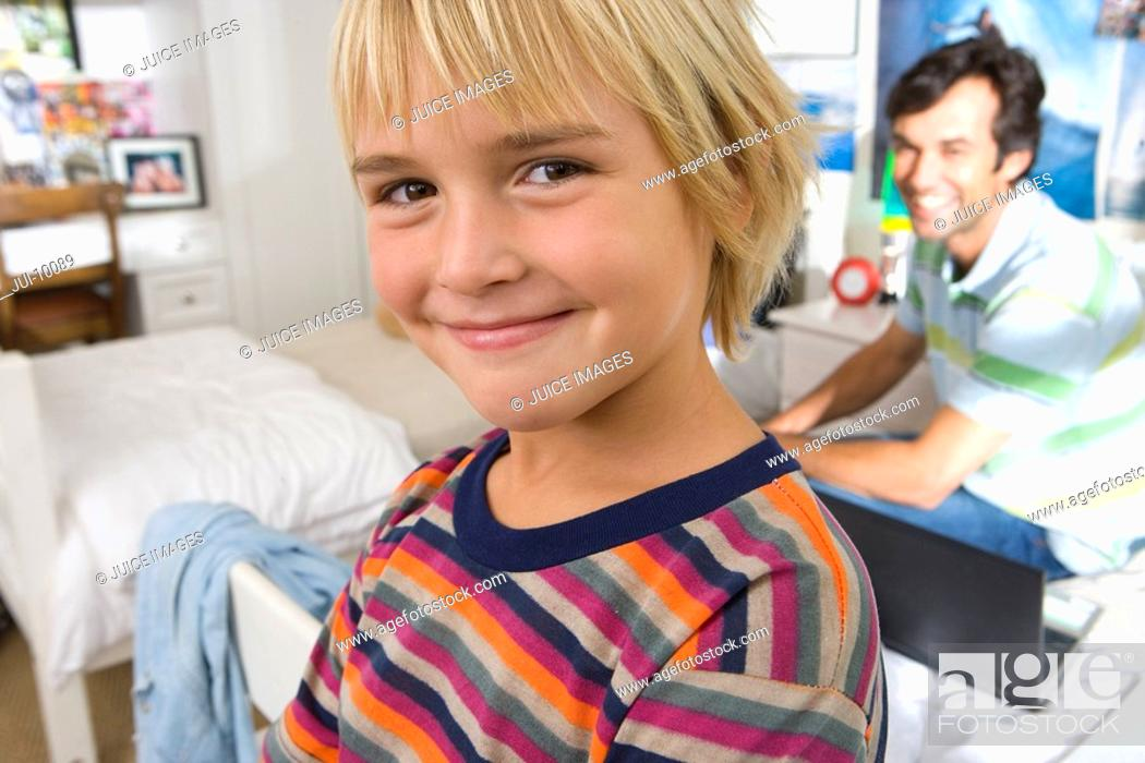 Stock Photo: Father and son 6-8 in bedroom, smiling, portrait, close-up of boy.