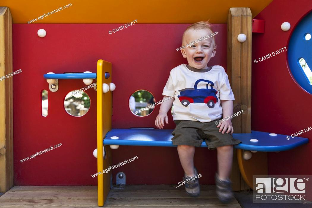 Stock Photo: A happy 1 year old boy sits in a playground house in the suberb of El Carmel, Barcelona, Cataluna, Spain.