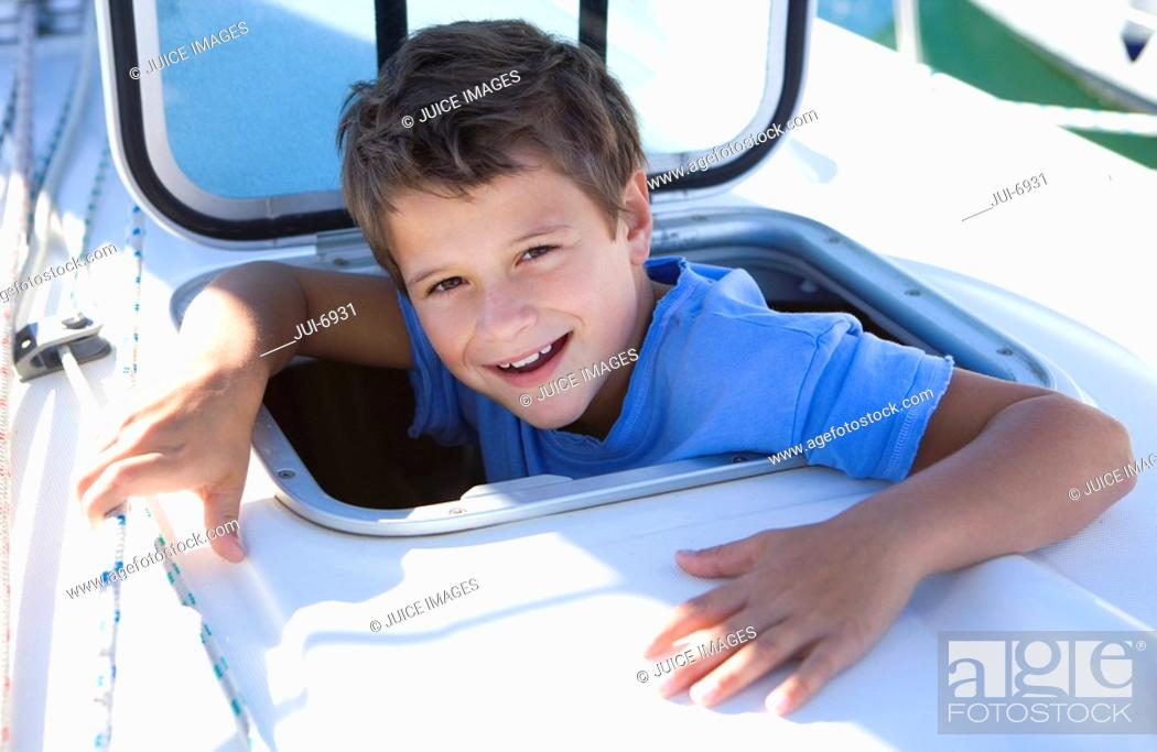 Stock Photo: Boy 8-10 sticking head through open sailing boat cabin window, smiling, close-up, portrait.