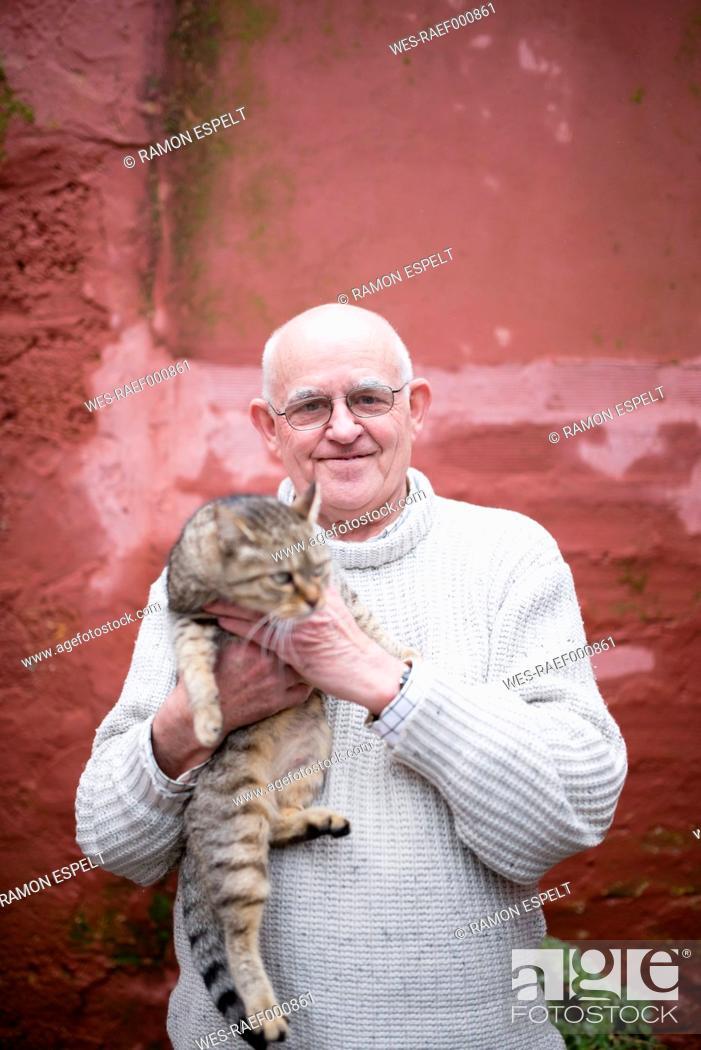 Stock Photo: Portrait of senior man holding tabby cat.