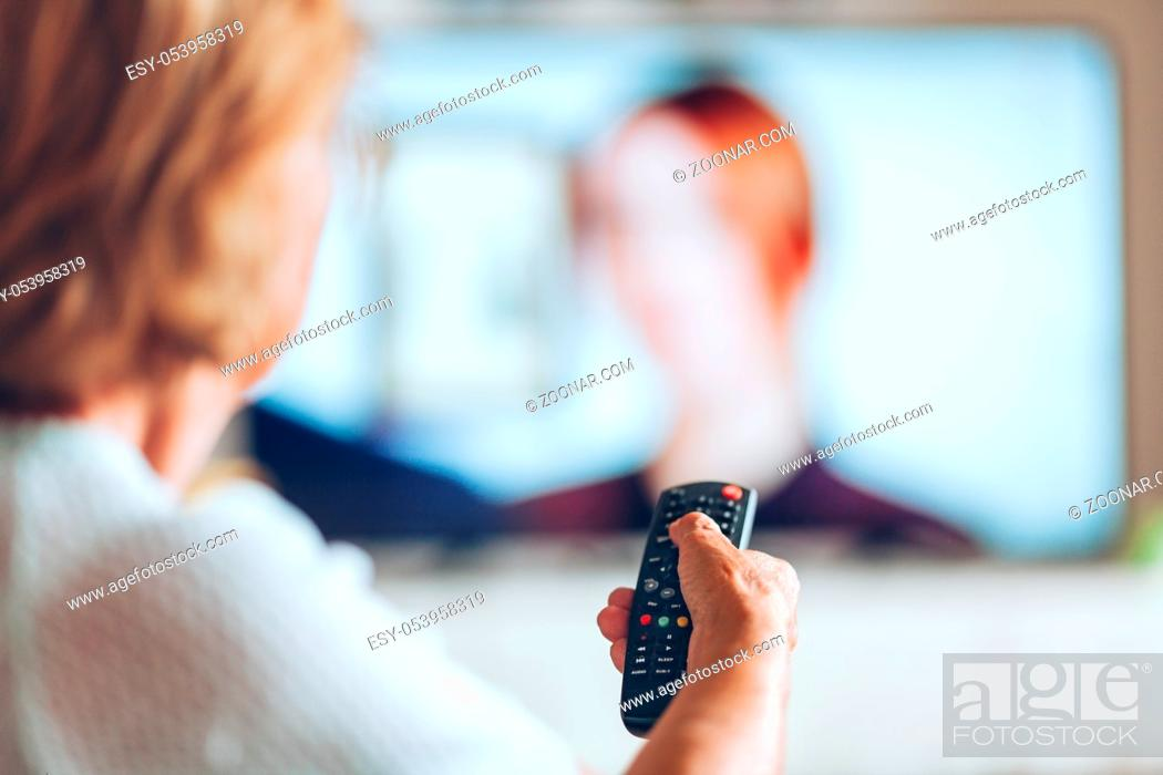 Stock Photo: Senior woman with remote control watching television.