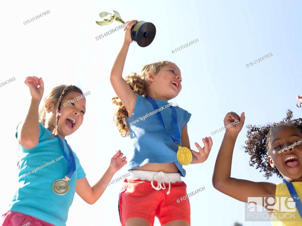 Stock Photo: Girls celebrating medals and trophies low angle view.