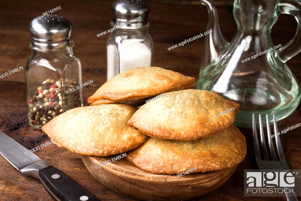 Photo de stock: fried sausage patties on rustic wooden tray on stage.