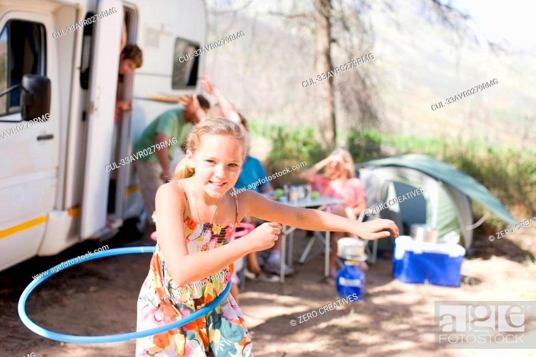 Stock Photo: Girl hula hooping at campsite.