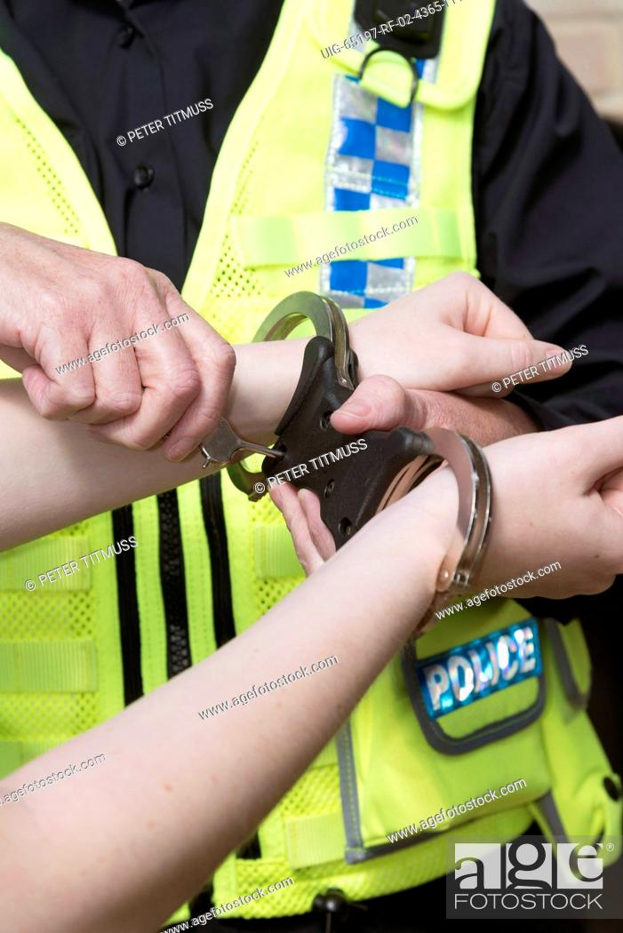 Photo de stock: Police officer unlocking handcuffs from a suspect's wrists.