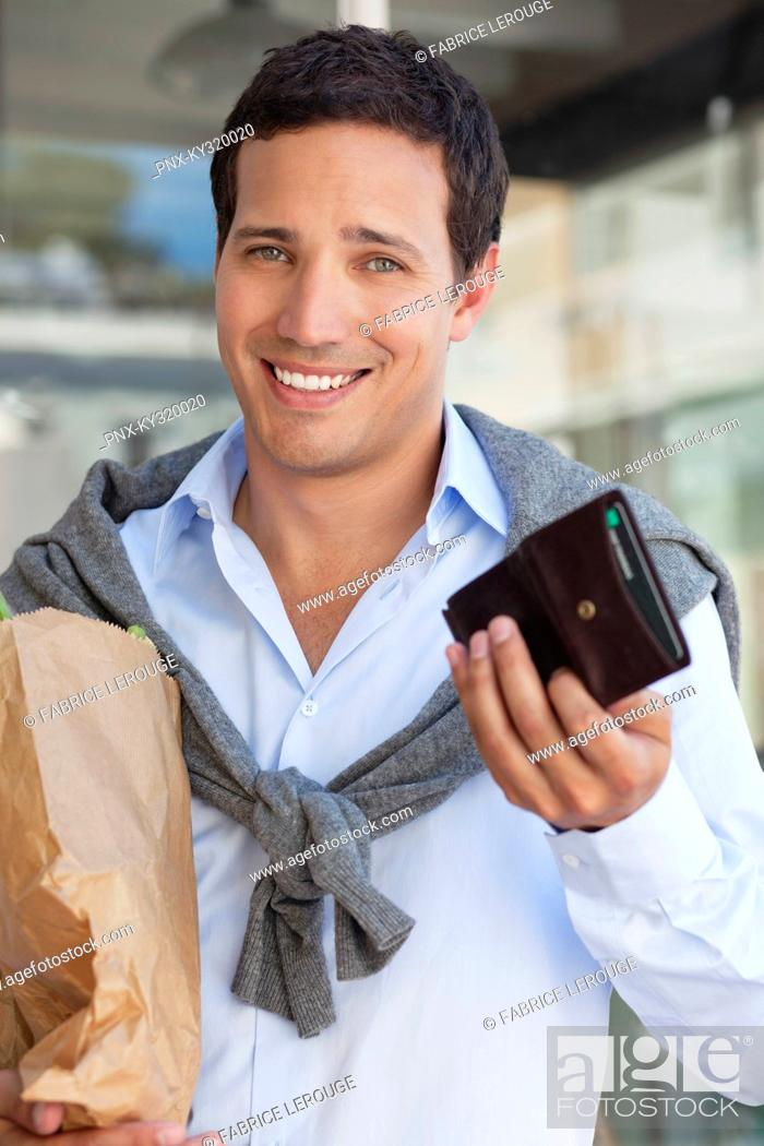 Stock Photo: Portrait of a man showing empty wallet with paper bag full of vegetables.