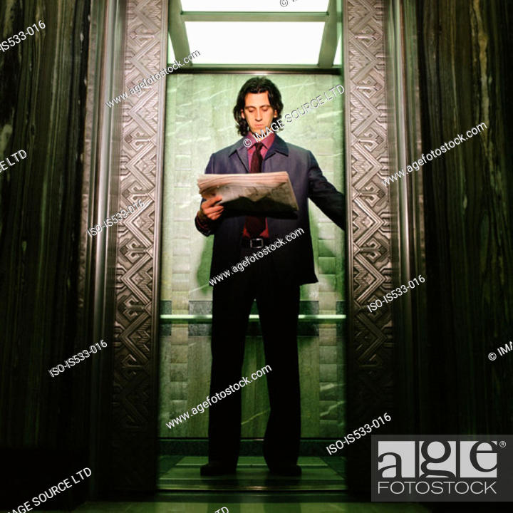 Stock Photo: Man reading newspaper in elevator.