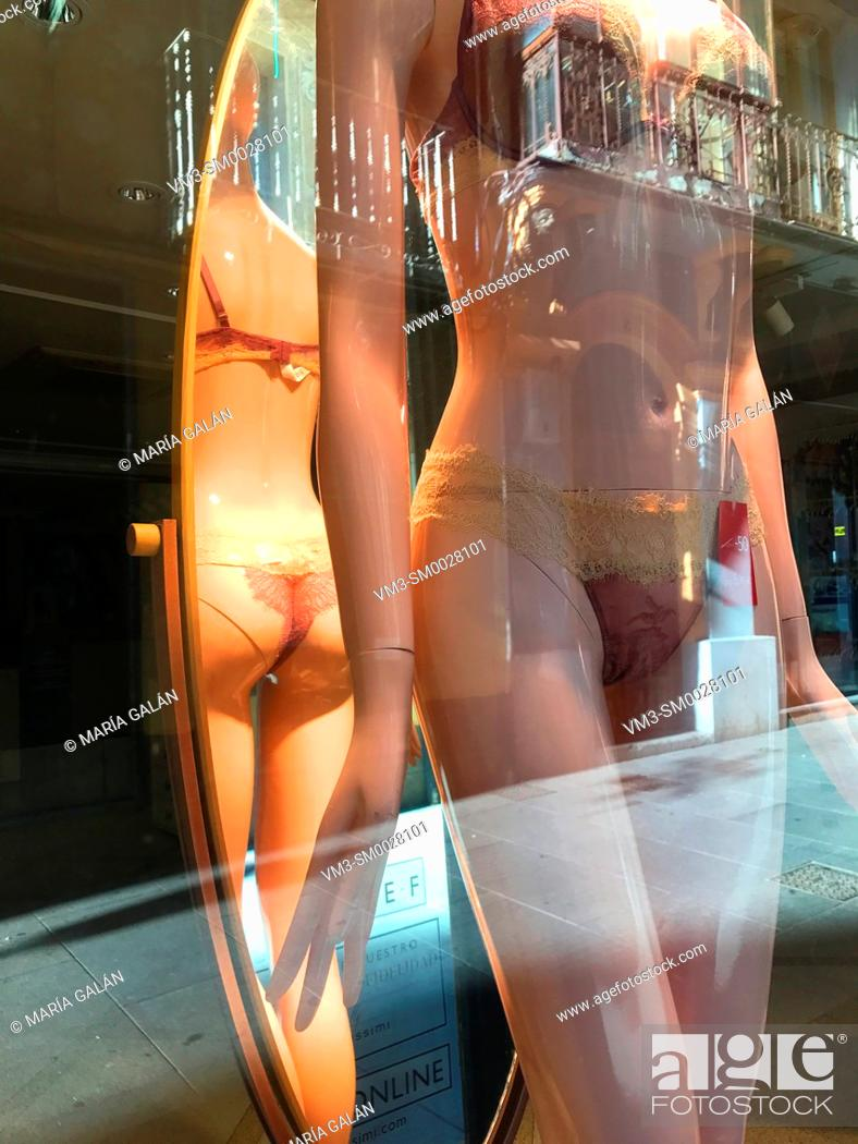 Stock Photo: Mannequin wearing sexy lingerie and its reflection on mirror in a shop window. Spain.