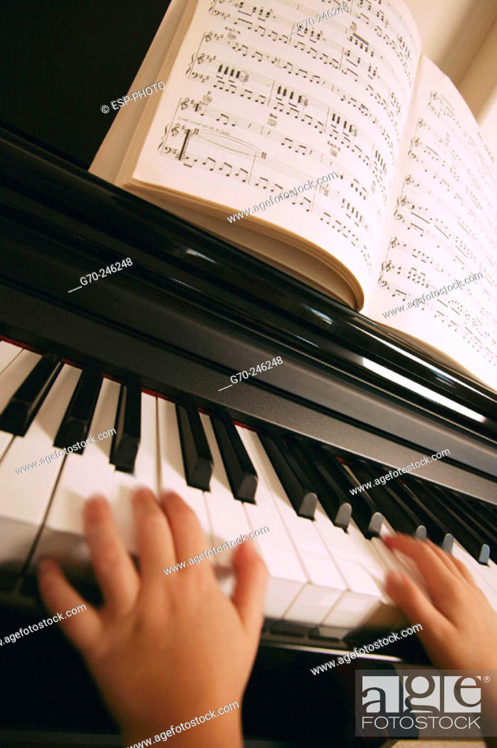 Stock Photo: Close Up of Young Girls Hands Playing the Piano.