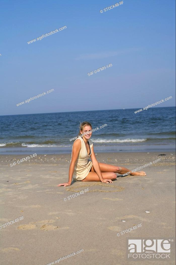 Stock Photo: Young woman sitting at the beach.