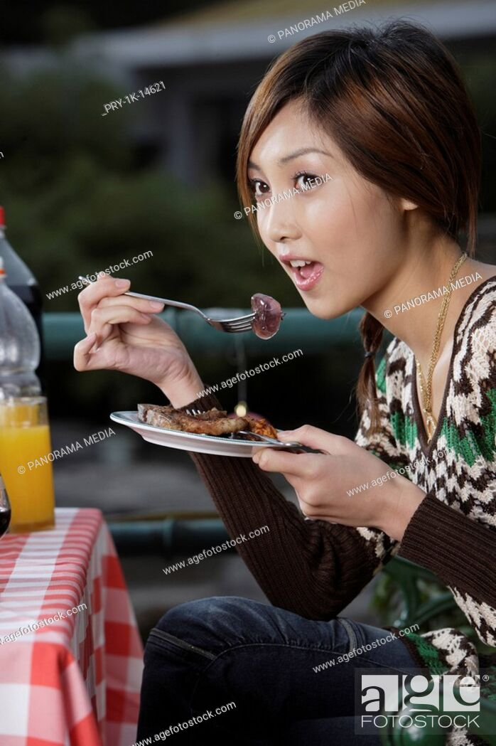 Imagen: Young woman eating food.