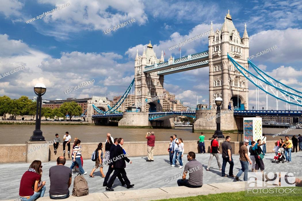 Stock Photo: England, London, Tower Bridge. People walking along the Thames path on the South Bank by Tower Bridge.