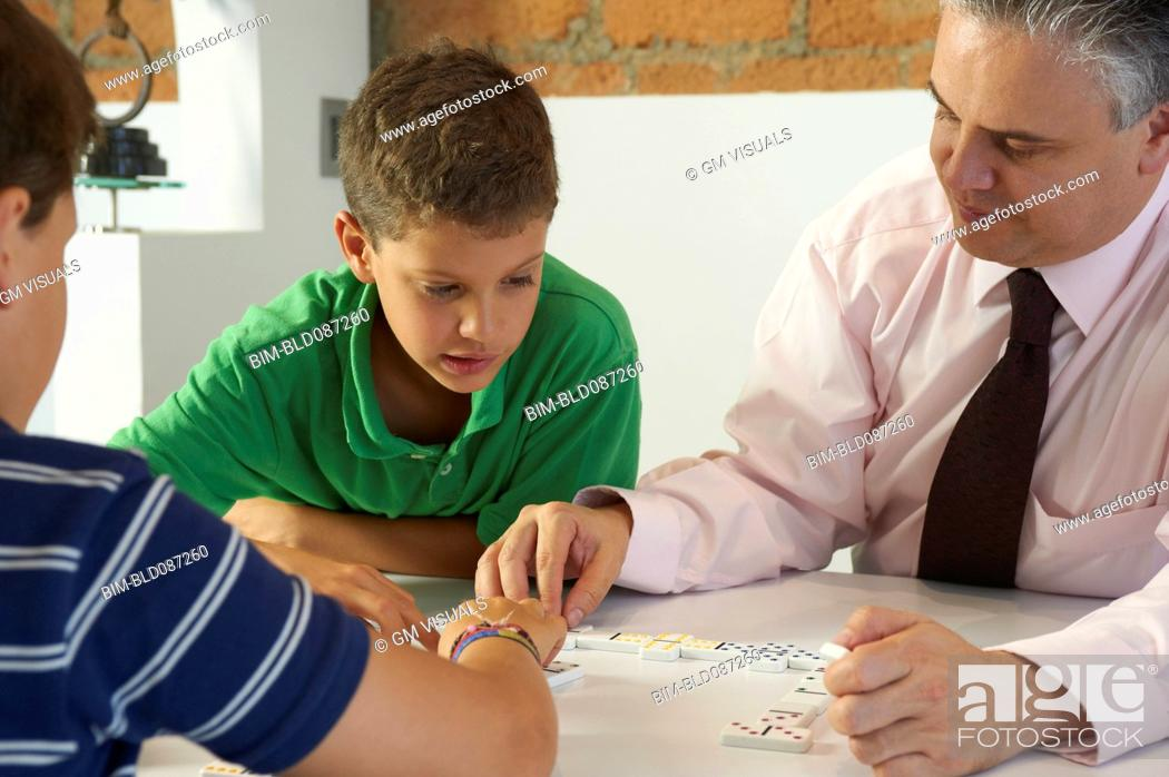 Imagen: Hispanic father playing dominoes with sons.