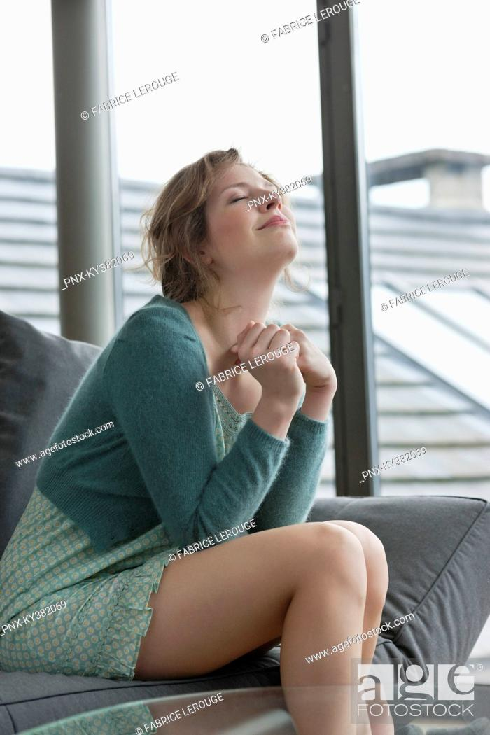 Stock Photo: Woman sitting on a couch with her eyes closed.