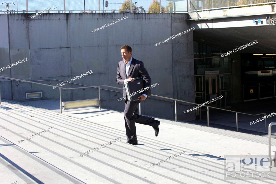 Stock Photo: Germany, Bavaria, Munich, Businessman walking on stairs with briefcase.