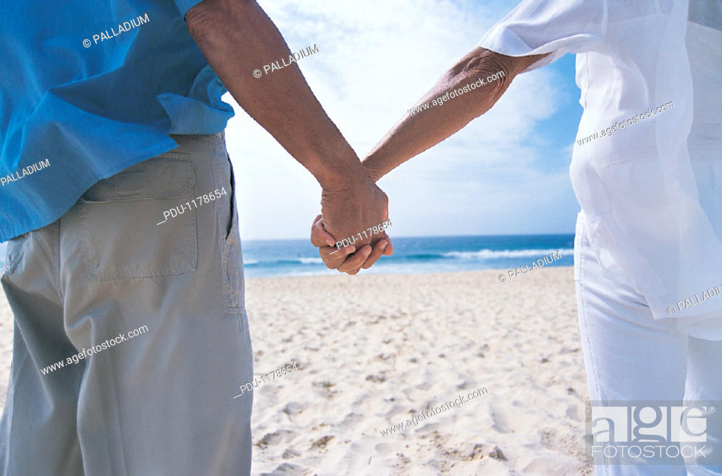 Stock Photo: Rear View Close up of a Senior Couple Holding Hands on the Beach.