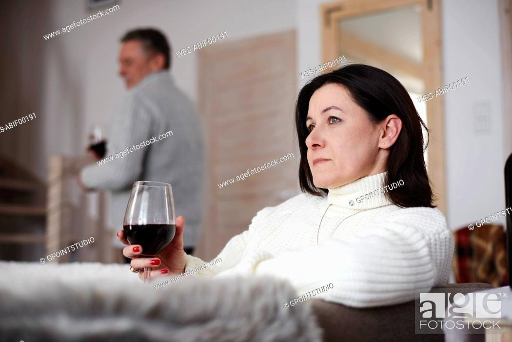 Stock Photo: Serious mature woman with glass of wine and man in background.