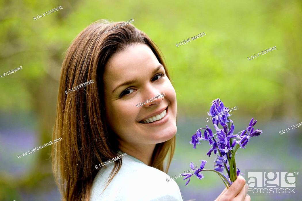 Stock Photo: Portrait of a young woman holding a bunch of bluebells, close-up.