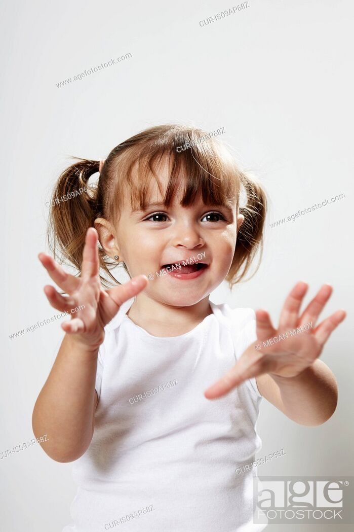 Imagen: Portrait of young girl with pigtails, with hands up.