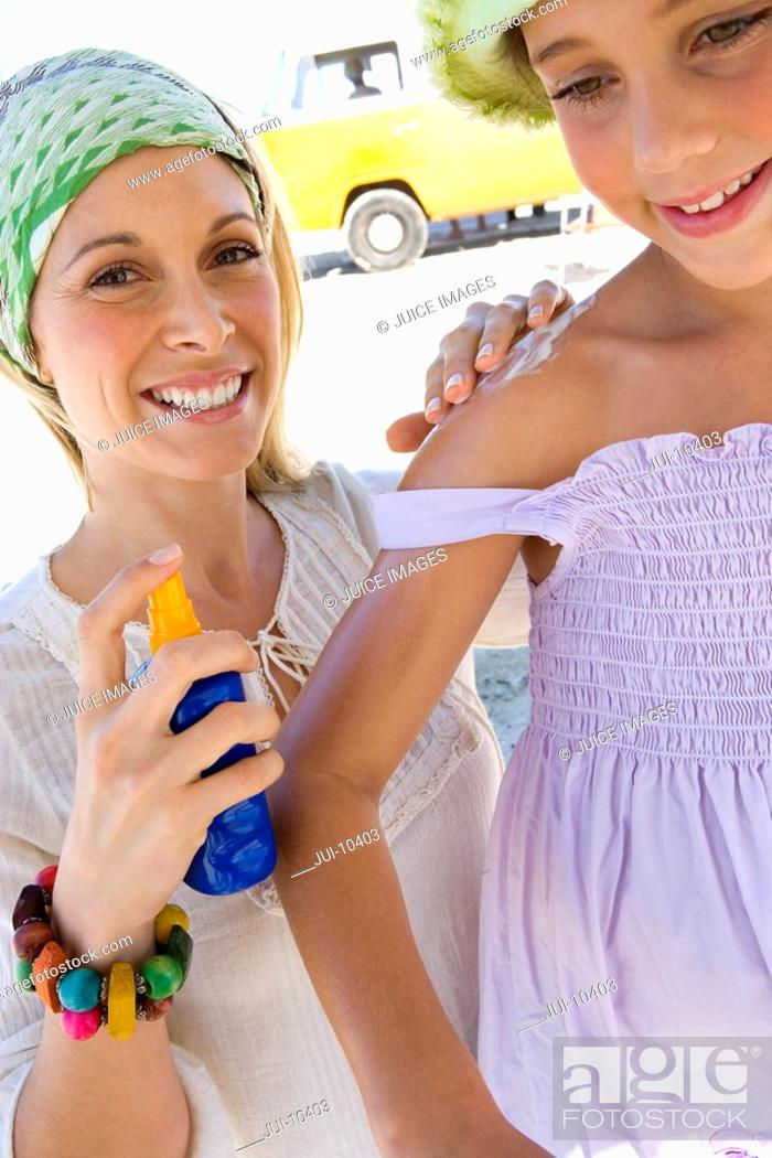 Stock Photo: Mother applying sunscreen to daughter 5-7 on beach, smiling, low angle view.