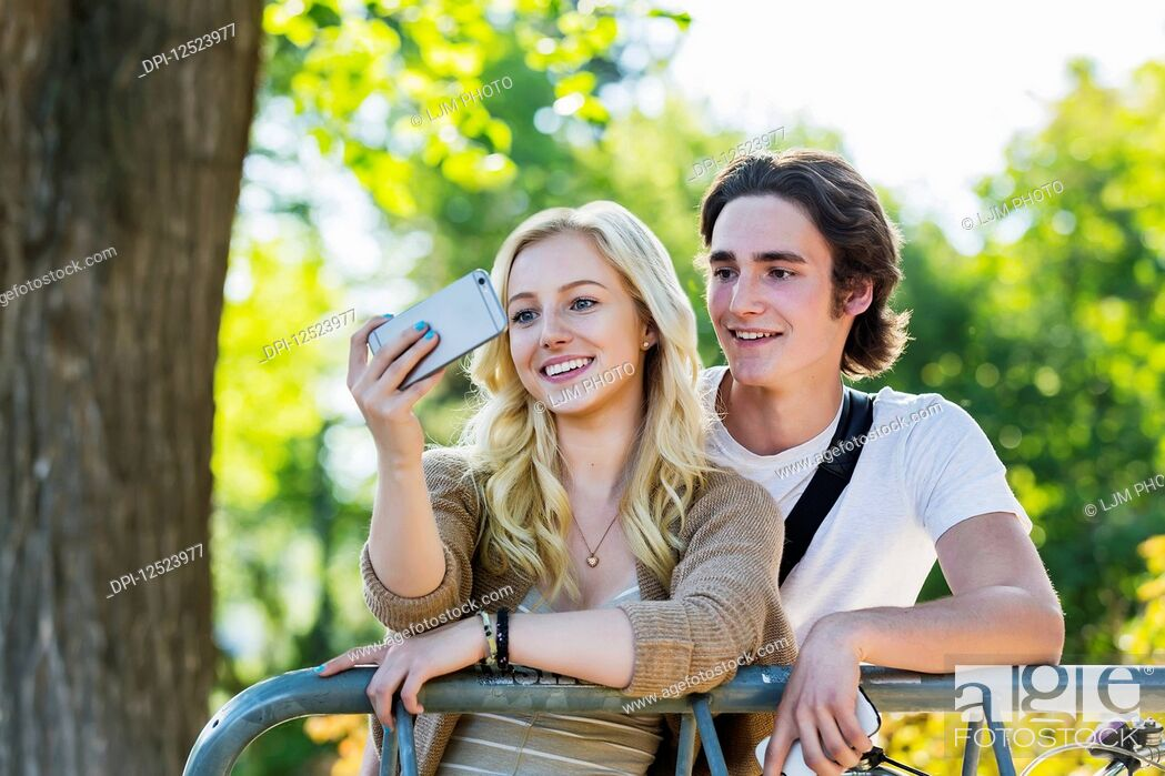 Stock Photo: A young couple stands together at a bike rack on the university campus taking a self-portrait with a smart phone; Edmonton, Alberta, Canada.
