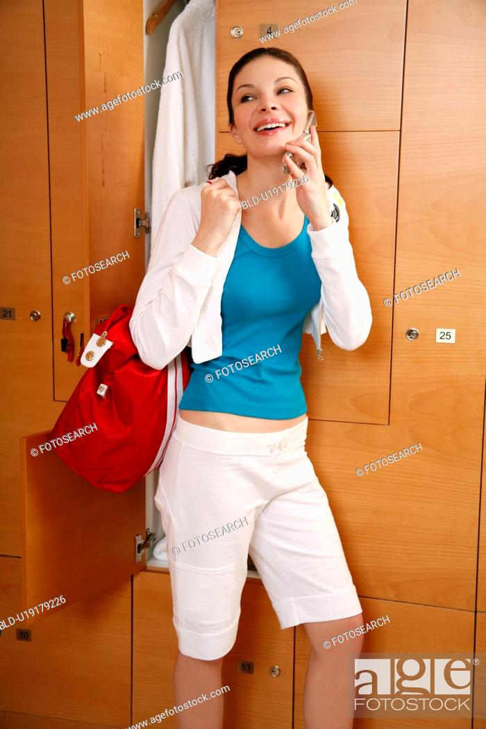 Stock Photo: Woman in locker room after work out talking on cell phone.