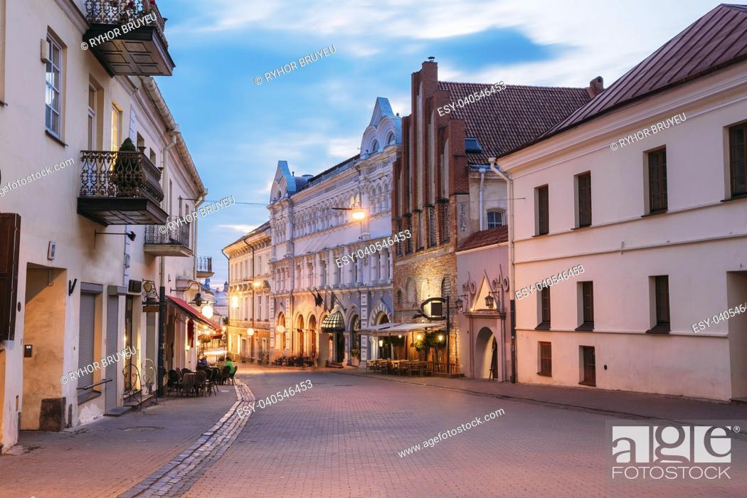 Imagen: Vilnius, Lithuania. View Of Illuminated Ausros Vartu Street, Famous Showplace Of Old Town With Outdoor Cafe And Ancient Red Brick Building In Summer Twilight.
