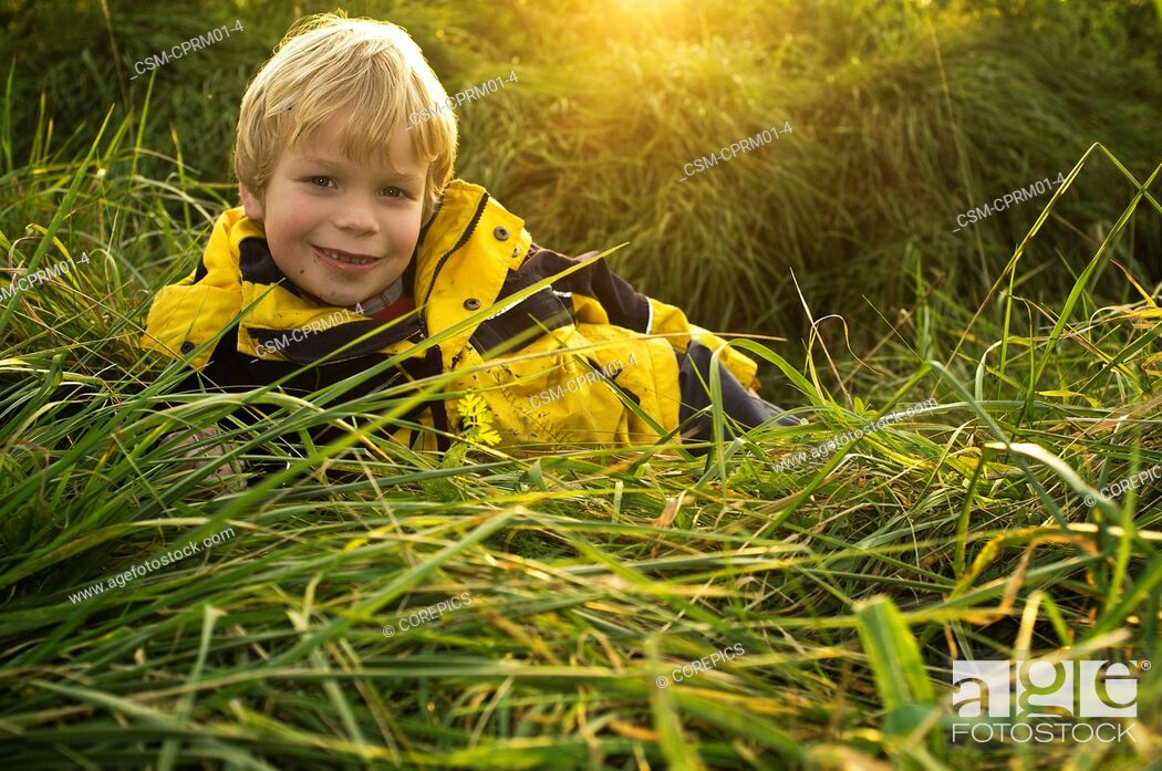 Stock Photo: Young boy, lying in the long grass of a ditch in a field, smiling.