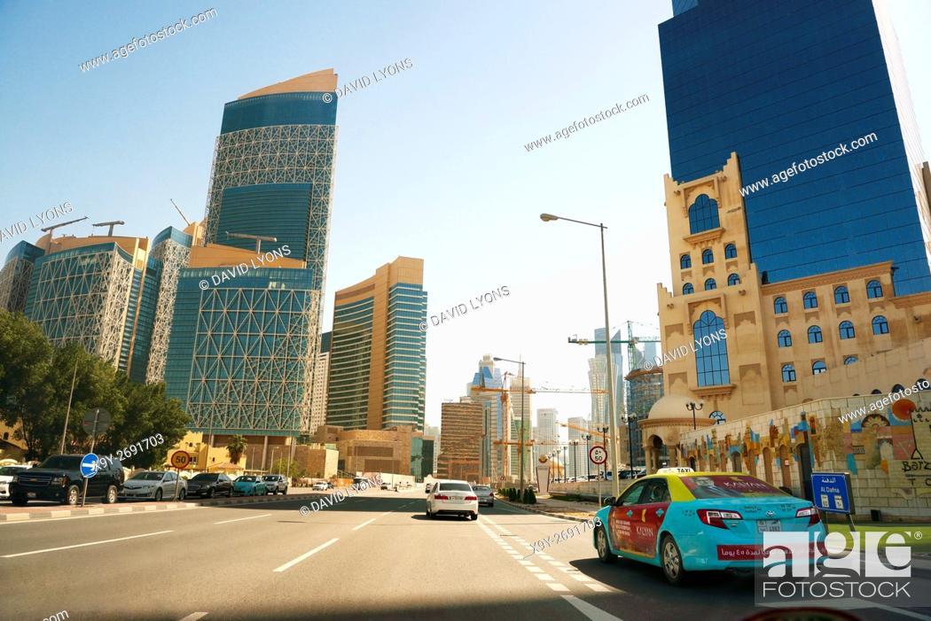 Stock Photo: Driving into central Doha, Qatar, on Majlis Al Taawon Street. Barzan Tower on right Qatar Petroleum District complex on left.