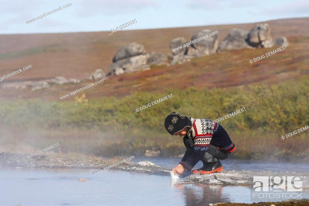 Stock Photo: Boy in hand-made nordic sweater and hat plays in the water at Serpentine Hot Springs, Bering Land Bridge National Preserve (National Park), Northwest Alaska.