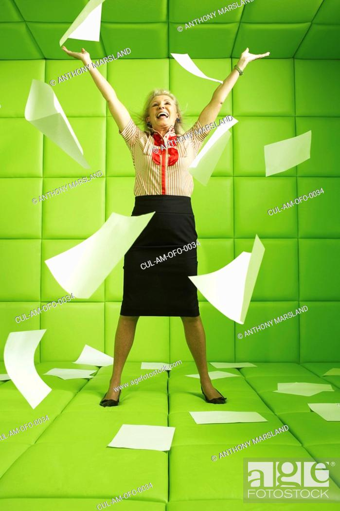 Stock Photo: Woman in green padded cell throwing papers.