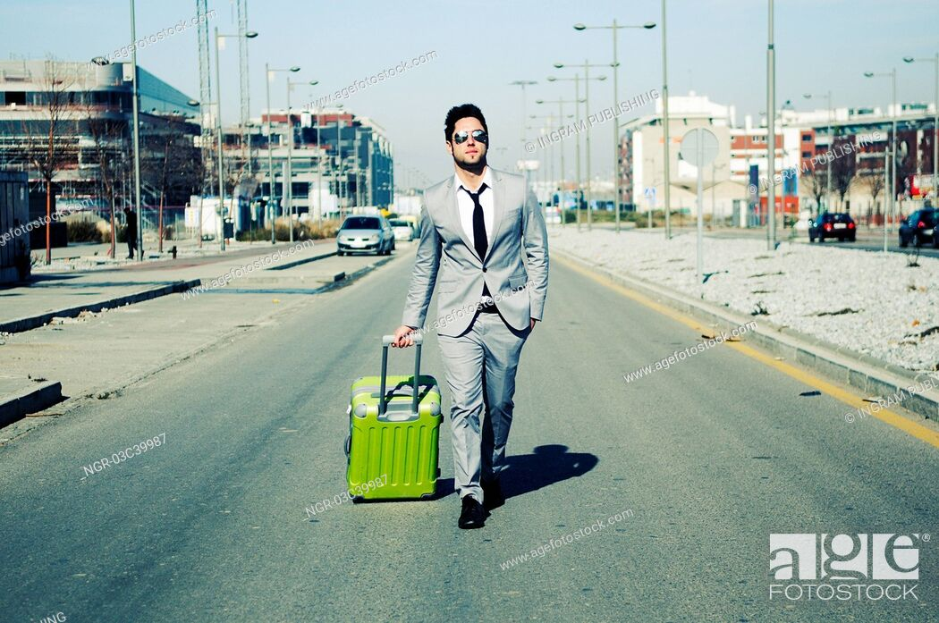 Stock Photo: Man dressed in suit and suitcase in the street.