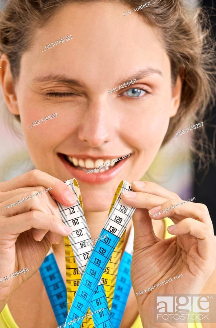 Stock Photo: beautiful young woman winking at photographer, holding a tape maesure and smiling.