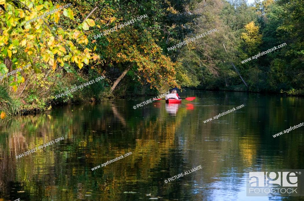 Stock Photo: 25 October 2020, Brandenburg, Schlepzig: A canoe is on its way on the main Spree in the Spreewald. The leaves of the trees at the water have turned an autumnal.