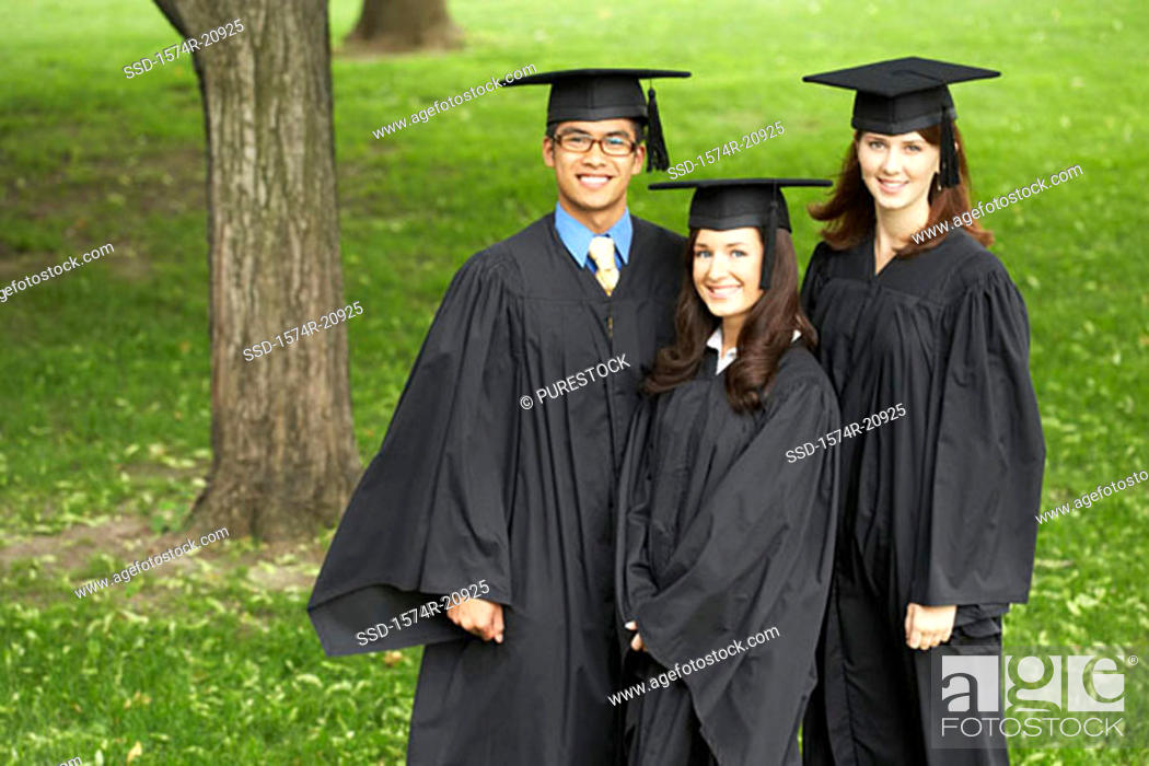 Stock Photo: Portrait of two female graduates and a male graduate smiling.