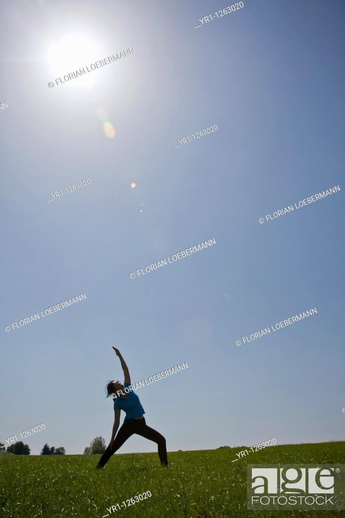 Stock Photo: Asian girl doing yoga workout on a field during summer. Shot in Aachen, Germany.