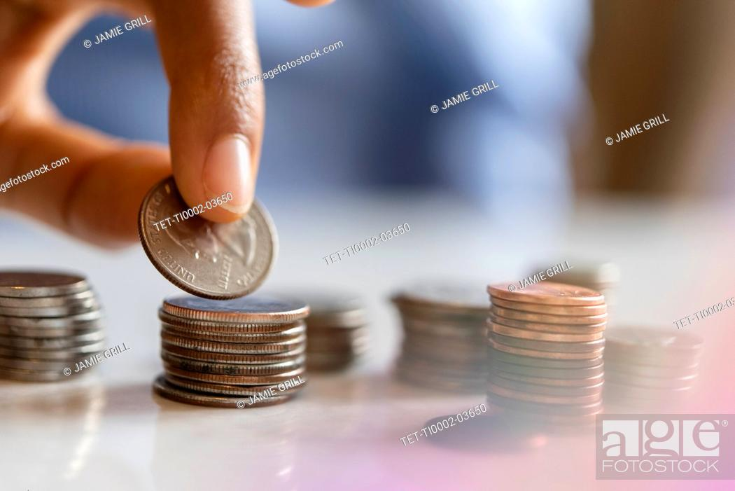Stock Photo: Hand of woman stacking coins.