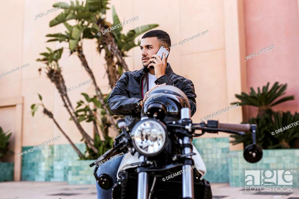 Imagen: Portrait of young man on the phone sitting on his motorbike.