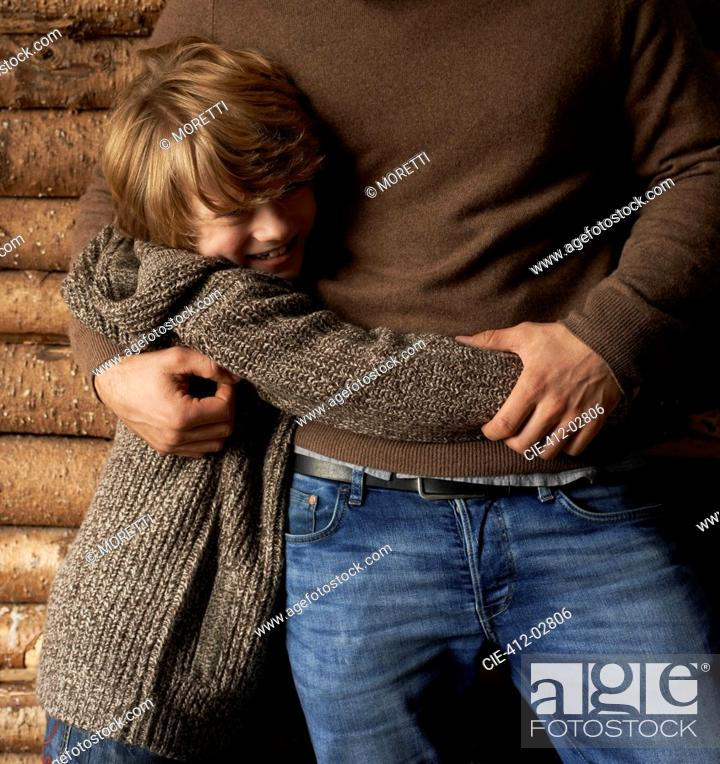 Stock Photo: Smiling son hugging father.