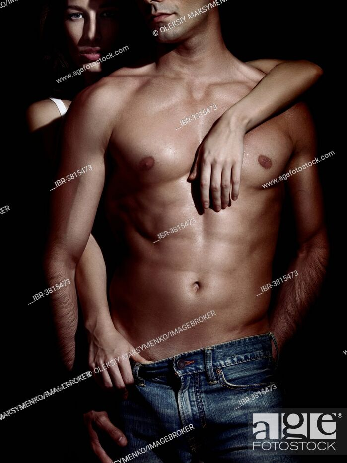 Stock Photo: Man with muscular bare torso embraced by a woman standing behind him.