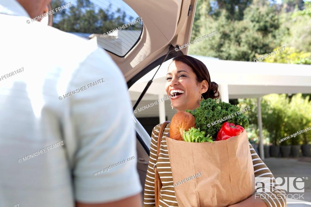 Stock Photo: Woman unloading groceries from car.
